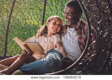 Smiling African American Girl Reading Book While Sitting In Swinging Hanging Chair With Granddad