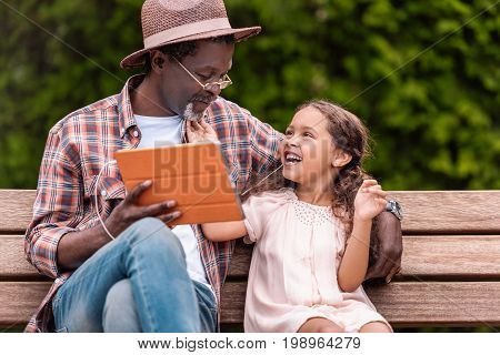 Happy African American Grandchild And Her Grandfather Listening Music On Digital Tablet While Sittin