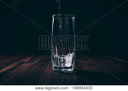 Water Poured Into An Empty Faceted Glass On A Black Background
