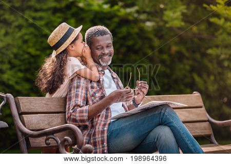 Little Adorable African American Grandchild Whispering To Her Smiling Grandfather While Sitting On B