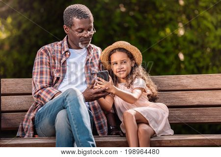 Smiling African American Girl And Her Grandfather Using Smartphone Sitting On Bench Together