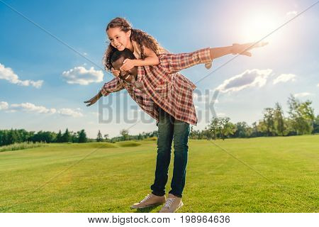African American Grandfather Giving Granddaughter Piggyback Ride On Green Lawn With Backlit