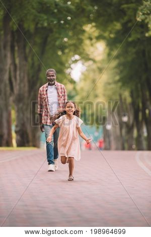 Happy African American Grandchild Running And Spending Time With Grandfather In Park