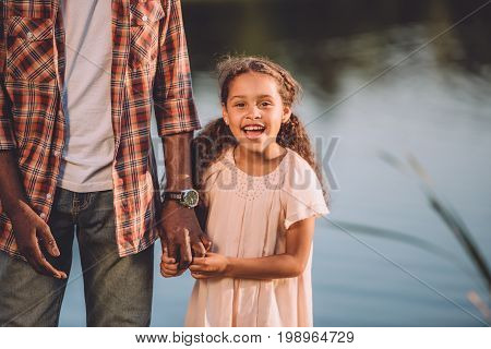 Cropped View Of Happy African American Granddaughter And Her Grandfather Holding Hands