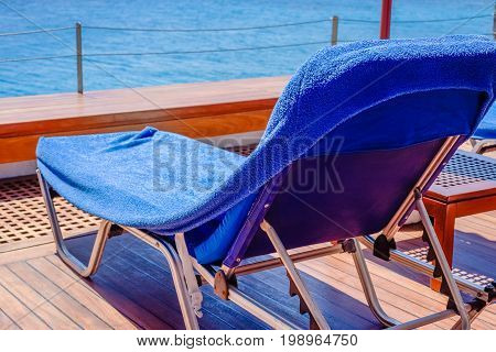 Chaise-longue on the wooden deck over the sea on the Greek resort close-up