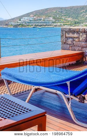 Chaise-longue and table on the wooden deck over the sea on a background of the Greek landscape close-up