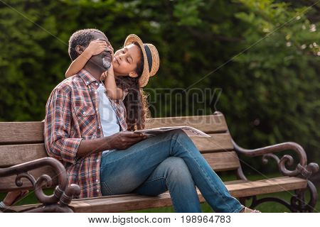 Little African American Girl Closing Eyes Of Her Grandfather Sitting On Bench In Park