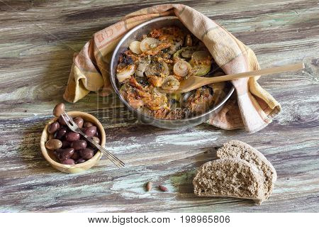 Fresh, baked ragout from different vegetables in a metal tray, olives and rusks on a wooden table close-up