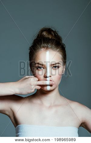 Young Attractive Teen Girl With Creative White Body Art Line On Face Showing Middle Finger, Isolated