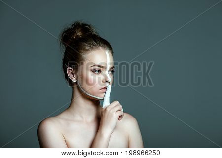 Young Beautiful Teen Girl With Creative White Body Art Line On Face Showing Shh Sign, Isolated On Gr