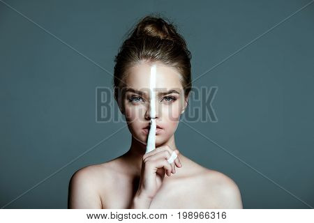 Young Beautiful Teen Girl With Creative White Body Art Line On Face Showing Hush Sign, Isolated On G