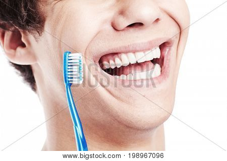 Close up of young man holding toothbrush near his toothy smile with perfect healthy white teeth isolated on white background - dental care concept