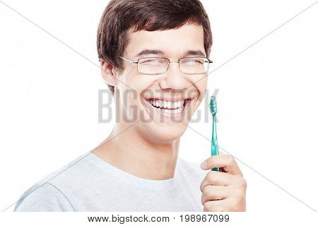 Face close up of young hispanic man wearing glasses holding toothbrush near his toothy smile with perfect healthy white teeth isolated on white background - dental care concept