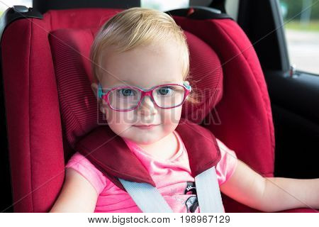 Little girl in glasses seating in the car safety seat