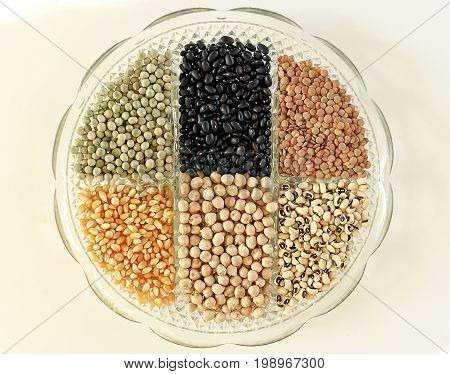 Glass tray with divisions filled with legumes and cereals isolated on a white background