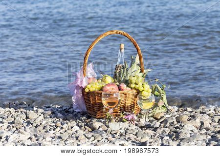 Different fruits in a wicker basket and wine in wineglasses against the background of the sea on a sunny day