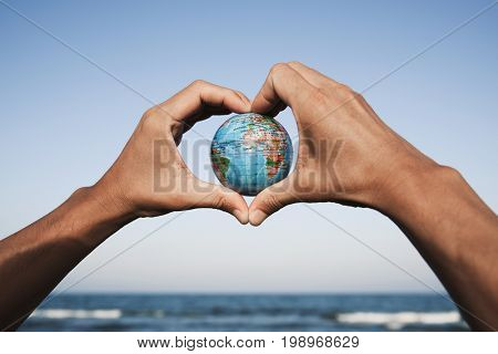closeup of a young caucasian man with a world globe in his hands forming a heart against the blue sky, in front of the sea