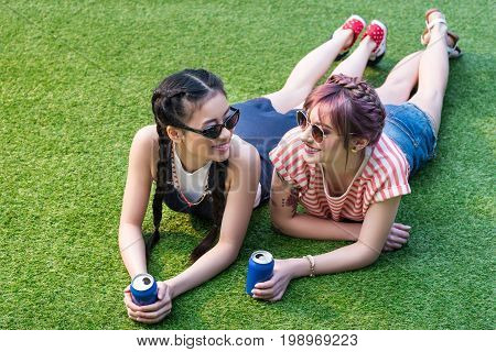 Beautiful Multiethnic Girls In Sunglasses Holding Soda Cans And Smiling Each Other While Lying On Gr
