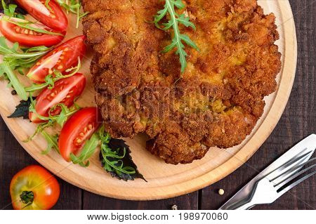 A large Viennese schnitzel and tomato salad on a cutting board on a dark wooden background. Top view. Close up