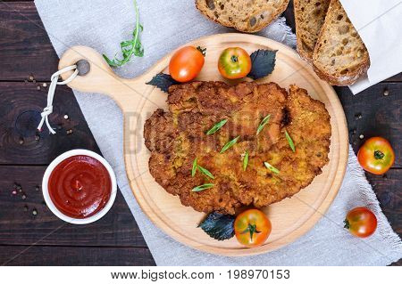 A large Viennese schnitzel on a cutting board on a dark wooden background. Top view.