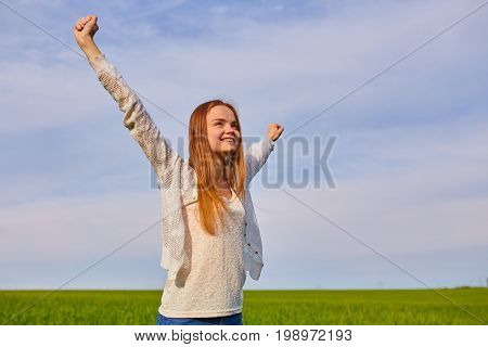 Girl With Open Arms On A Green Wheat Field