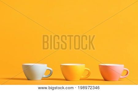 Little teacups aligned on a bright background