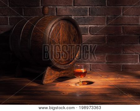 Glass Of Cognac With Barrel On Wooden Table