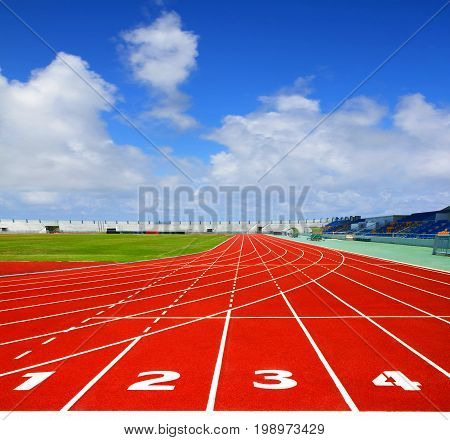 Sport running track. Lanes 1 2 3 4 of a red racing track with blue sky background image for design and other.