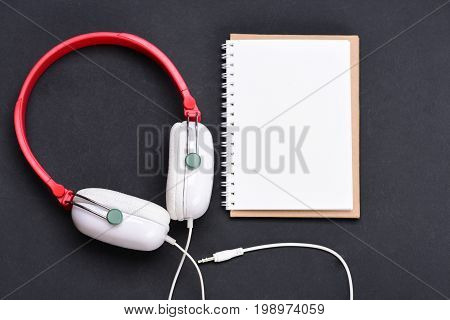 Headphones in white and red color with empty notebook. Headset for music and blank page copy space. Music accessories and note taking concept. Modern and stylish earphones on dark background topview