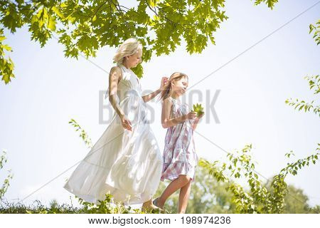 Side view of mother and daughter walking in nature. Mom carefully touching her girls hair.