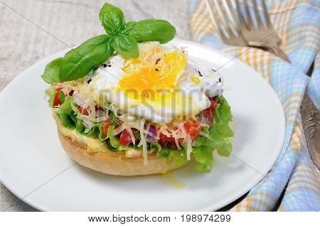 Sandwich with vegetable filling and egg poached sprinkled cheese