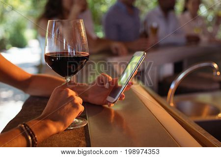 Hand of woman using mobile phone while having a glass of wine in restaurant