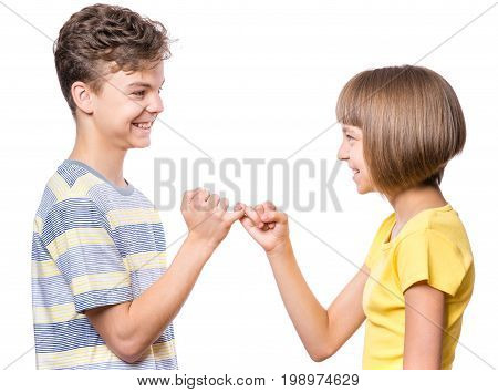 Teen boy and girl on the little finger, hands making promise as a friendship concept. Portrait of happy brother and sister, isolated on white background.