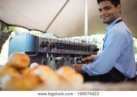Portrait of smiling waiter making cup of coffee from espresso machine in restaurant