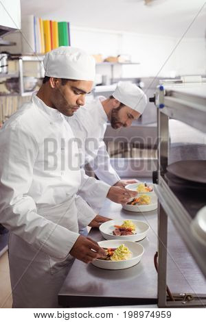 Two chefs garnishing food in commercial kitchen at restaurant