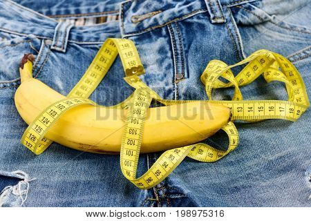 Jeans belt loops zipper and pocket close up. Health and male sexuality concept. Mens denim pants crotch with banana imitating male genitals. Banana wrapped with yellow measure tape on jeans.