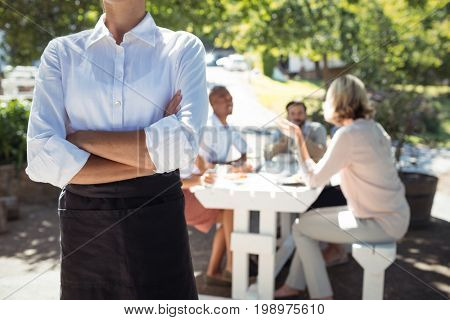 Mid section of waitress standing with arms crossed in restaurant