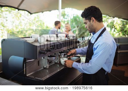 Waiter making cup of coffee from espresso machine in restaurant