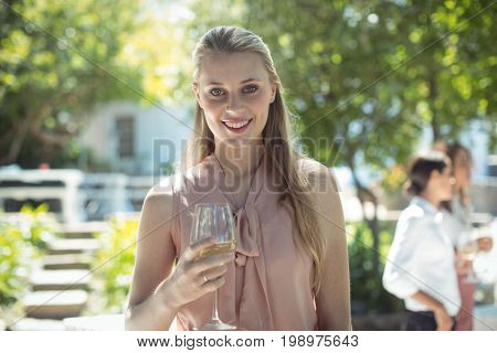Portrait of smiling woman holding glass of wine in restaurant