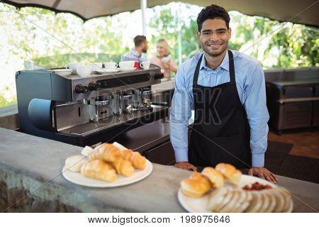 Portrait of smiling waiter standing near counter at restaurant