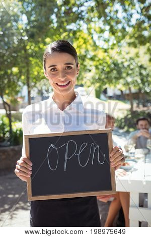 Smiling waitress standing with open sign board in restaurant