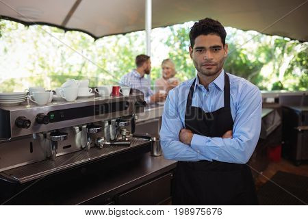 Portrait of male waiter standing with arms crossed in the restaurant