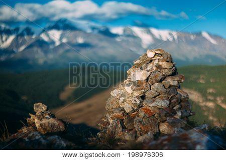 Stone landmark on Landmannalaugar trek and snow mountains beyond,