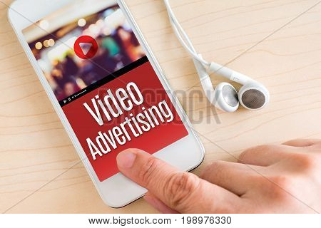 Hand touch smart phone and ear phone with Video Advertising word on wood table Digital Marketing concept