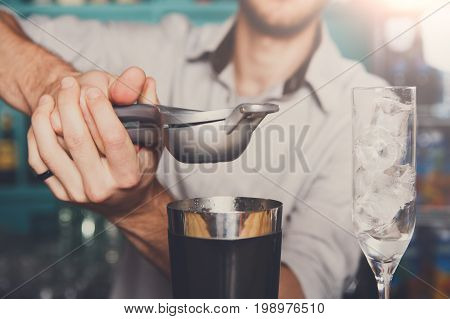 Unrecognizable bartender making cocktail with lime, squeezing it into mixing glass for citrus drink.