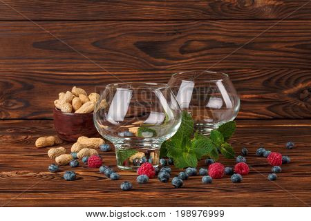 Two empty big glasses on a dark wooden background with green leaves of mint, pink sappy raspberries, black succulent bilberries and peanuts in a brown bowl. Fresh berries and mint on a wooden table.