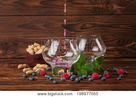 Two glasses with juice on a dark wooden background with green leaves of mint, pink sappy raspberries, black succulent bilberries and peanuts in a brown bowl. Fresh berries and mint on a wooden table.