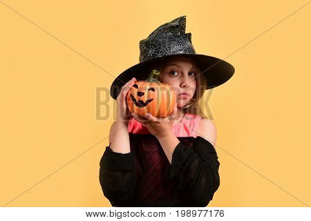 Halloween And Autumn Holiday Concept. Kid In Black Witch Hat