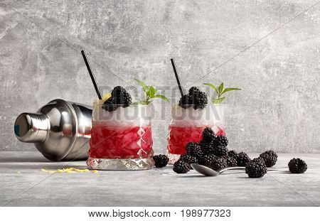 Two glasses with fruit cocktails, black drinking straws, fresh blackberries, green sappy leaves of mint and silver metallic shaker on a grey light background.