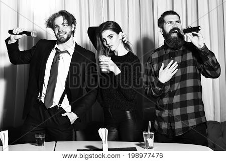 Group of friends celebrating at karaoke party on white curtain. Two bearded men hipsters with beard in red plaid shirt and business suit singing. Pretty girl or beautiful woman drinking cocktail